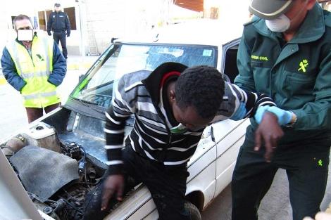 El joven inmigrante es ayudado por un agente a salir del capó. | EL MUNDO