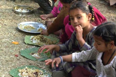 Niños indios desplazados comen en el campo de refugiados de Damana.