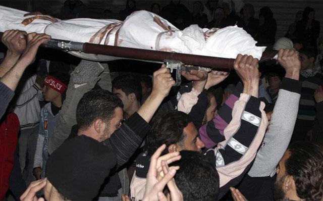 Varios hombres acarrean un fallecido en Damasco.| Reuters