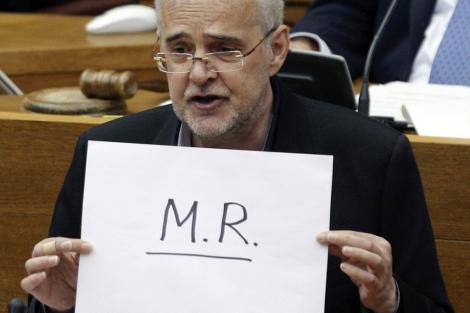 El socialista Francesc Signes exhibe un sobre con las iniciales de Rajoy.   Efe