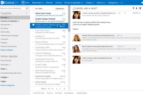 Dos jóvenes en sus ordenadores utilizan el nuevo correo de Outlook