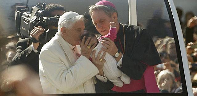 El secretario personal del Papa le da a besar un bebé en el Papamóvil. | Reuters