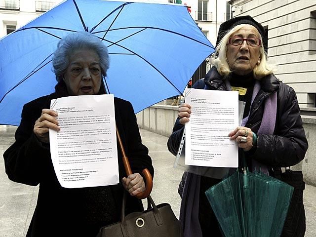 Las presidentas de dos asociaciones de mujeres muestran el documento entregado hoy en el Congreso.   Fernando Alvarado / Efe