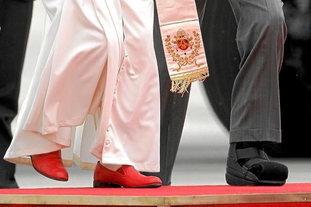 El Papa calza sus zapatos rojos, regalo de un artesano mexicano, a su llegada a Madrid para asistir a la JMJ. A la derecha, el zapato ortopédico del Rey Juan Carlos I. | Alberto di Lolli