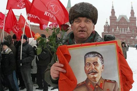 Un hombre del partido comunista, con una foto de Stalin. Archivo.| Afp