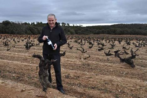 El viticultor José Alberto Calvo Casajús posa con uno de sus vinos junto a una cepa. | Foto: I.M.