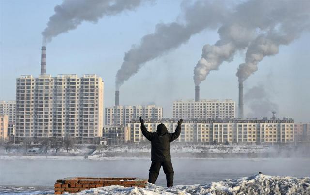 Un anciano hace ejercicios frente a unas fábricas en Jilin, China. | Reuters
