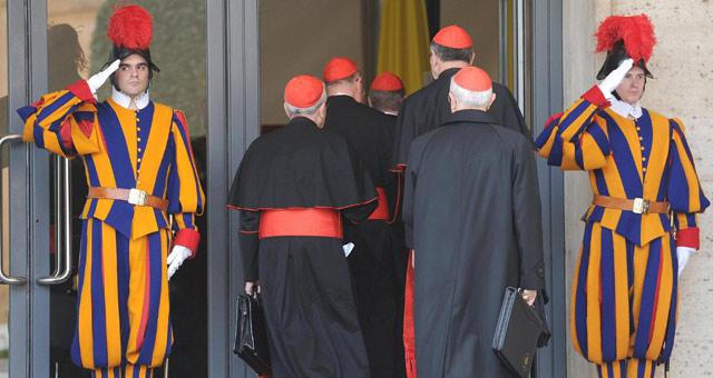 Dos guardias suizos saludan a un grupo de cardenales. | Efe