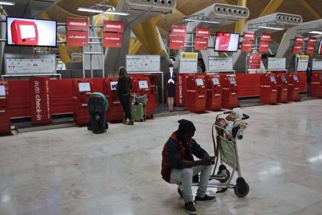 Un pasajero, sentado en un carro de equipajes en el aeropuerto de Barajas. | Efe
