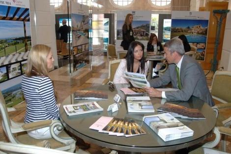 Un expositor atiende a una potencial compradora en la feria inmobiliaria para rusos.   Javier Martín