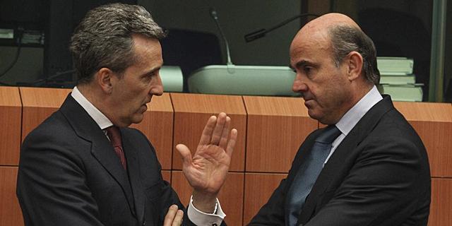 El ministro italiano, Vitorrio Grilli (i), charla con De Guindos durante el Eurogrupo.   Efe
