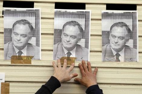 Un manifestante pega carteles con la cara de González Pons en su casa. | Reuters