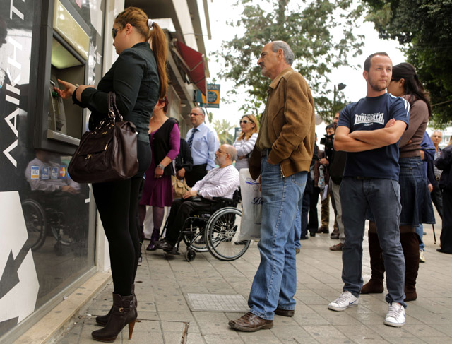 Clientes de Popular Bank hacen cola para sacar su dinero en Nicosia. | Afp