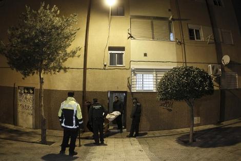 La policía saca de la casa el cadáver de la mujer.  Alberto Di Lolli