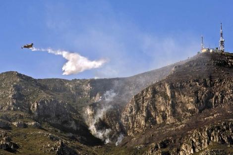 Un hidroavión arroja agua en el frente del incendio forestal de Barx. | Efe