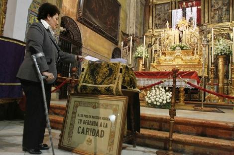 Una mujer da un donativo ante la Soledad de San Lorenzo. | Carlos Márquez