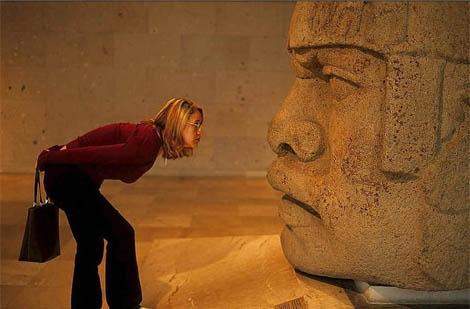 Una visitante en el Museo Antropológico de México ante una cabeza olmeca.   Tino Soriano