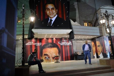 Un enorme cartel de Bassem Youssef a la puerta de un teatro. | Afp