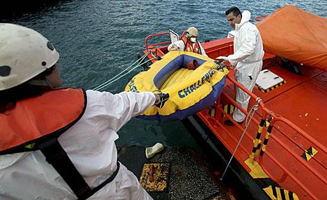 Personal de Salvamento Marítimo sube a tierra una lancha hinchable. | A. Carrasco Ragel / Efe