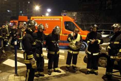 Un grupo de bomberos, junto al edificio incendiado en Aubervilliers.   Afp