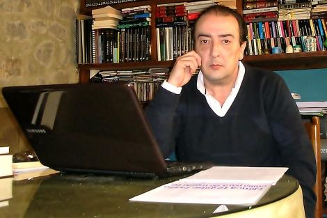 El novelista Javier Ochoa posa junto al borrador de su novela.