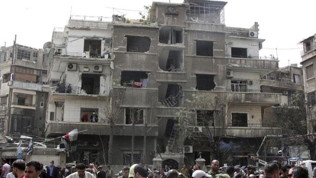Varios ciudadanos observan un edificio quemado. | Efe