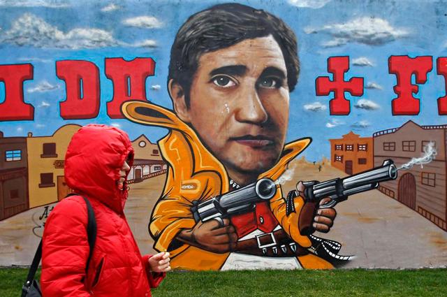 Una mujer camina frente a un mural que convierte al presidente Pedro Passos Coelho en pistolero. | Reuters