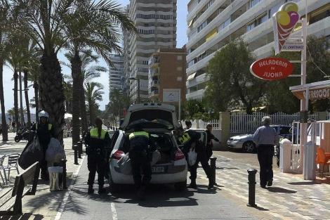 Los agentes guardan el material incautado en su coche. | E.M.