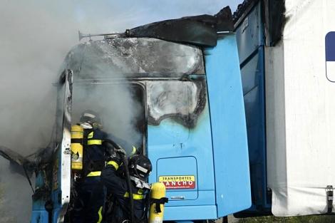 Los bomberos extinguen el fuego en el camión incendiado. | Sergio Enriquez