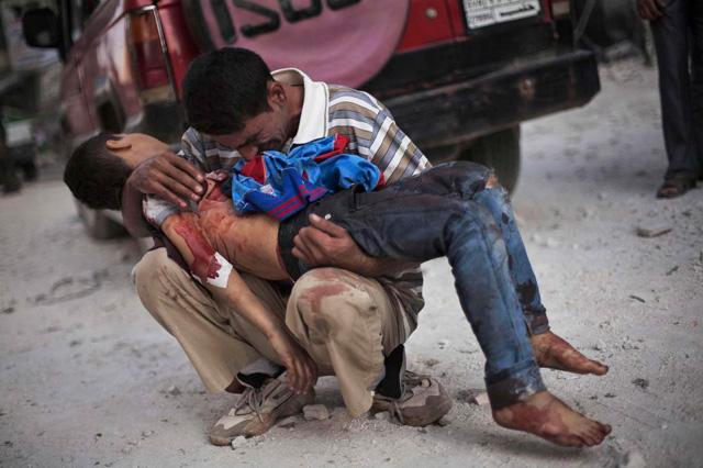 Un hombre sirio sostiene el cuerpo sin vida de su hijo cerca del hospital Dar El Shifa, en Aleppo.   Manu Brabo/ AP