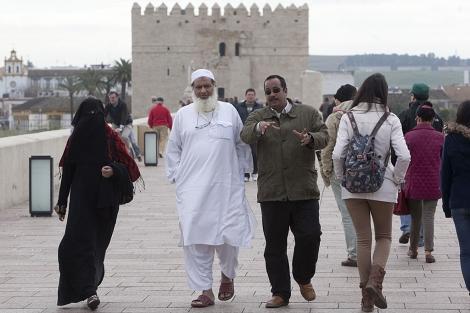 Paseantes musulmanes por el puente romano de Córdoba. | Madero Cubero