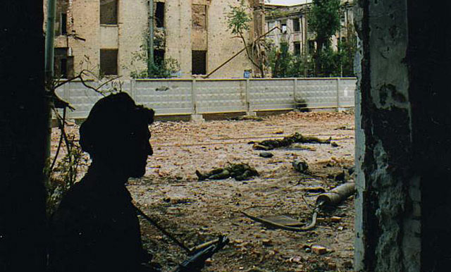 Un soldado checheno vigila una calle donde se encuentran cadáveres de rusos descuartizados en los 90 en Rusia.  Igor Mijaliov