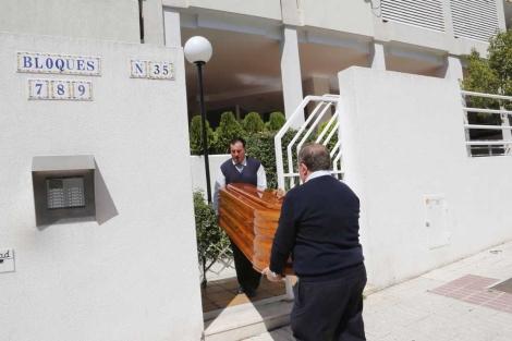 Efectivos de los servicios funerarios trasladan el cuerpo de la madre del menor.   A. Pastor