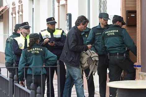 Uno de los forenses accede a la casa del suceso en Almonte.   Efe