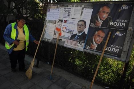 Una mujer limpia junto a un cartel electoral.   Afp