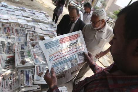 Un hombre lee El-Watan, este domingo en la plaza Tahrir. | Reuters