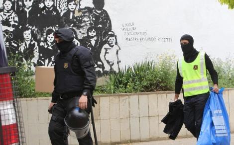 Dos agentes trasladan material requisado en el Ateneu Llibertari de Sabadell.   Efe