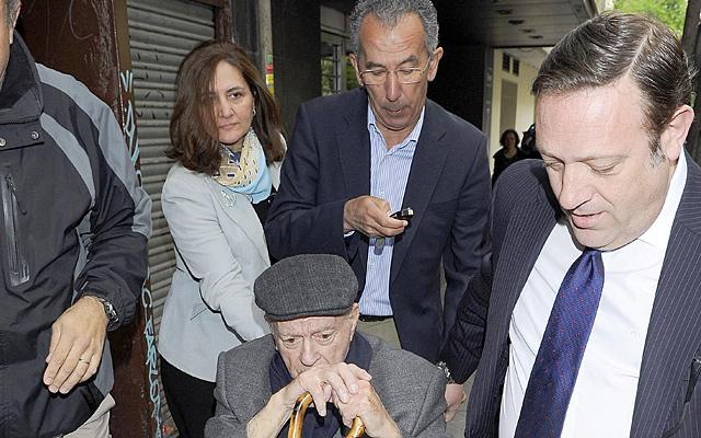 Alfredo Di Stefano a la salida de los juzgados en una silla de ruedas empujada por su hijo