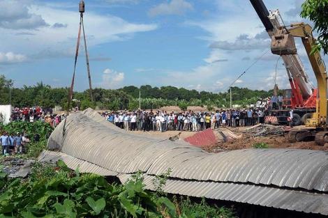 Una grúa intenta levantar el cobertizo desplomado en Camboya. | Afp