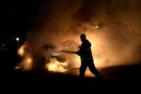 Un bombero intenta apagar un coche incendiado en Estocolmo.   Afp