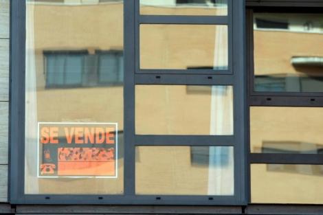 Una cartel de 'Se vende' colocado en la ventana de un piso de Madrid. | Diego Sinova