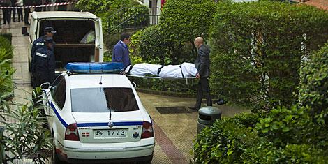 Los servicios sanitarios sacan el cuerpo de la mujer asesinada..  Efe