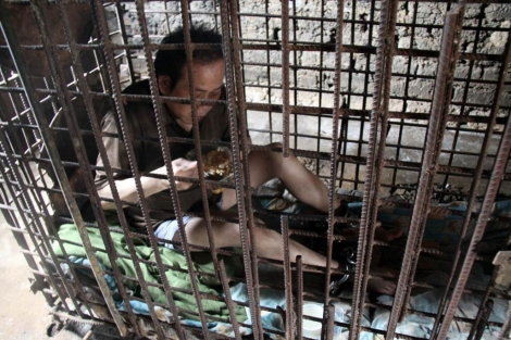 Wu Yuanhong come encerrado en su jaula. | Afp