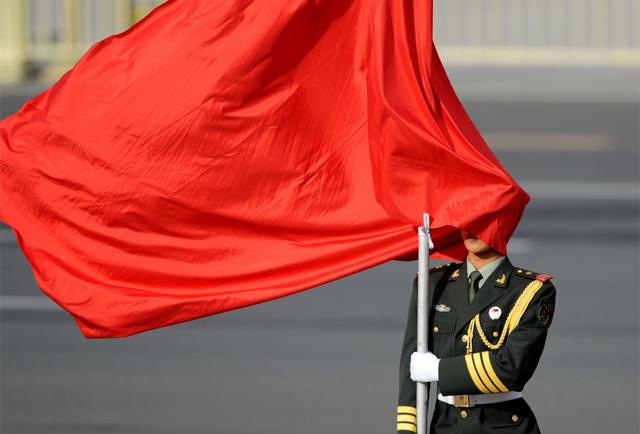 soldado envuelto por la bandera china. | Afp
