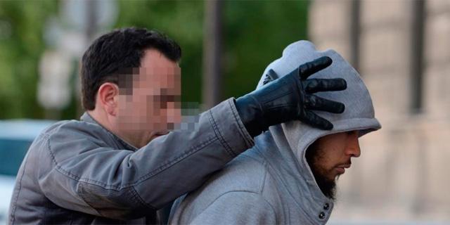 El detenido, custodiado por un policía