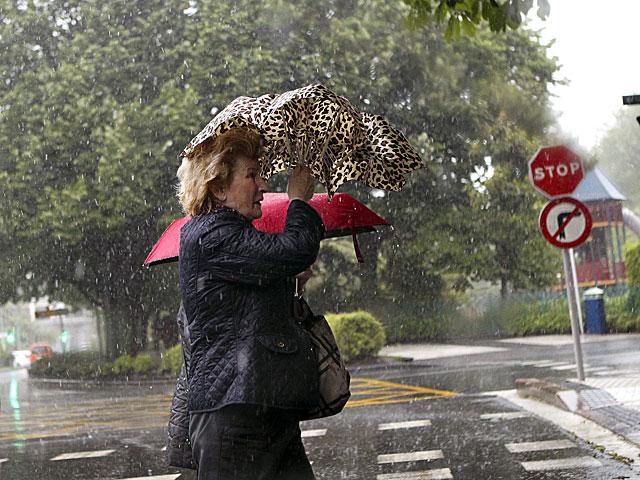 Una mujer se enfrenta a la lluvia este viernes en San Sebastián. | Javier Etxezarreta / Efe