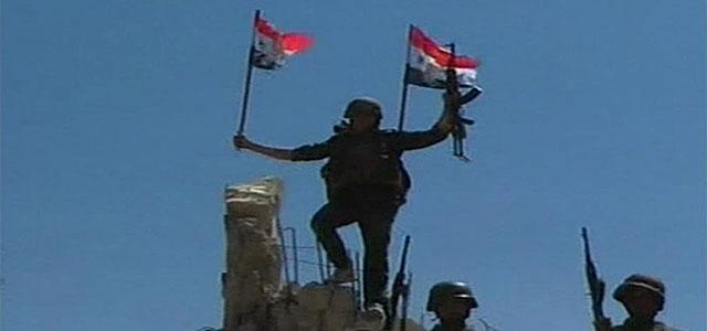 Un soldado sirio con una bandera del país, en Quseir.  Reuters