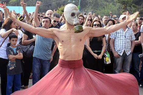 Un manifestante baila con una máscara antigas en el parque Gezi en Estambul. | Efe