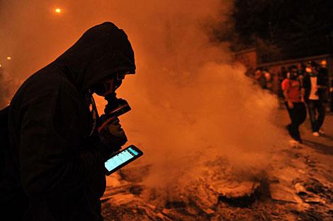 Un manifestante turco usa Facebook en el móvil.   Afp