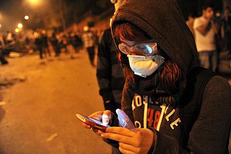 Una joven informa desde su móvil cerca de Taksim en Estambul.   Afp
